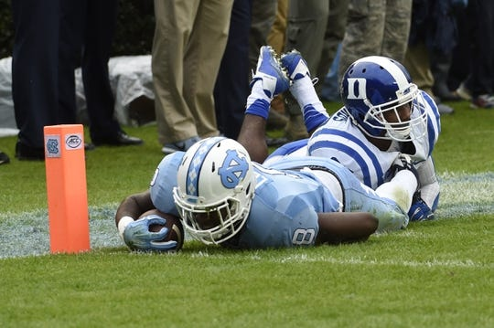 Nov 7, 2015; Chapel Hill, NC, USA; North Carolina Tar Heels running back T.J. Logan (8) is tackled near the goal line by Duke Blue Devils safety DeVon Edwards (27) in the forest quarter at Kenan Memorial Stadium. Mandatory Credit: Bob Donnan-USA TODAY Sports