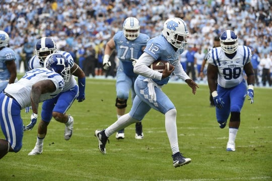 Nov 7, 2015; Chapel Hill, NC, USA; North Carolina Tar Heels quarterback Marquise Williams (12) scores a touchdown as Duke Blue Devils safety DeVon Edwards (27) and defensive tackle Mike Ramsay (99) defend in the firs quarter at Kenan Memorial Stadium. Mandatory Credit: Bob Donnan-USA TODAY Sports