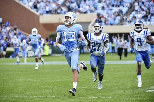 Nov 7, 2015; Chapel Hill, NC, USA; North Carolina Tar Heels wide receiver Mack Hollins (13) scores a touchdown as Duke Blue Devils safety DeVon Edwards (27) and cornerback Jeremy McDuffie (9) defend in the second quarter at Kenan Memorial Stadium. Mandatory Credit: Bob Donnan-USA TODAY Sports