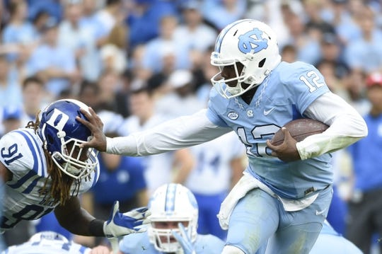 Nov 7, 2015; Chapel Hill, NC, USA; North Carolina Tar Heels quarterback Marquise Williams (12) runs as Duke Blue Devils defensive end Marquies Price (91) defends in the second quarter at Kenan Memorial Stadium. Mandatory Credit: Bob Donnan-USA TODAY Sports