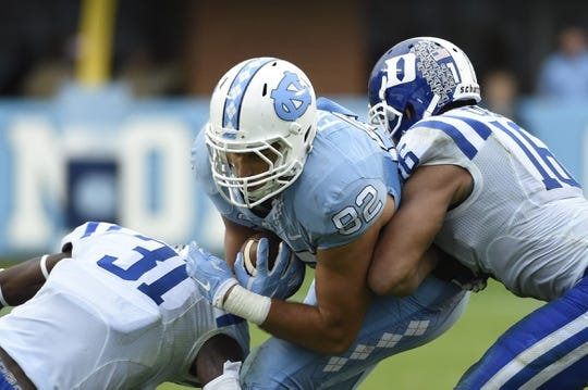Nov 7, 2015; Chapel Hill, NC, USA; North Carolina Tar Heels tight end Brandon Fritts (82) with the ball as Duke Blue Devils cornerback Breon Borders (31) and safety Jeremy Cash (16) defend in the third quarter at Kenan Memorial Stadium. Mandatory Credit: Bob Donnan-USA TODAY Sports