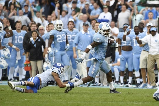 Nov 7, 2015; Chapel Hill, NC, USA; North Carolina Tar Heels cornerback Des Lawrence (2) intercepts the ball as Duke Blue Devils wide receiver Anthony Nash (83) defends in the third quarter at Kenan Memorial Stadium. Mandatory Credit: Bob Donnan-USA TODAY Sports