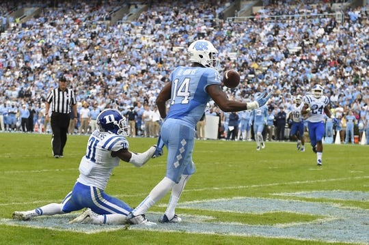 Nov 7, 2015; Chapel Hill, NC, USA; North Carolina Tar Heels wide receiver Quinshad Davis (14) catches a touchdown as Duke Blue Devils cornerback Breon Borders (31) defends in the third quarter at Kenan Memorial Stadium. Mandatory Credit: Bob Donnan-USA TODAY Sports
