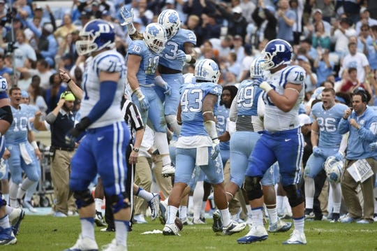 Nov 7, 2015; Chapel Hill, NC, USA; North Carolina Tar Heels linebacker Jeff Schoettmer (10) celebrates with linebacker Cayson Collins (23) and teammates after recovering a fumble in the first quarter at Kenan Memorial Stadium. Mandatory Credit: Bob Donnan-USA TODAY Sports
