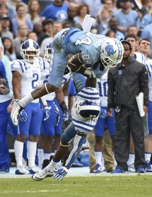 Nov 7, 2015; Chapel Hill, NC, USA; North Carolina Tar Heels wide receiver Bug Howard (84) catches the ball as Duke Blue Devils safety DeVon Edwards (27) defends in the second quarter at Kenan Memorial Stadium. Mandatory Credit: Bob Donnan-USA TODAY Sports
