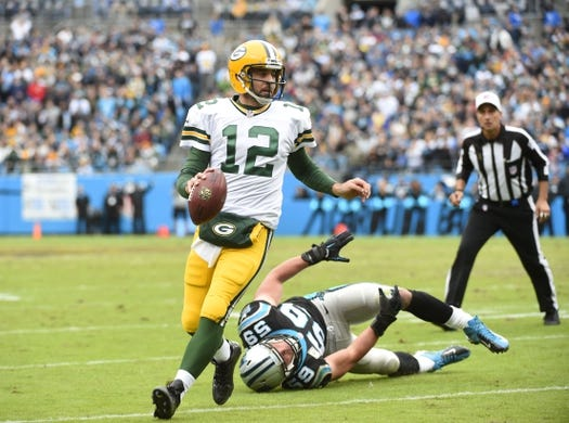 Nov 8, 2015; Charlotte, NC, USA; Green Bay Packers quarterback Aaron Rodgers (12) scrabbles before throwing a touchdown pass as Carolina Panthers middle linebacker Luke Kuechly (59) defends in the first quarter at Bank of America Stadium. Mandatory Credit: Bob Donnan-USA TODAY Sports