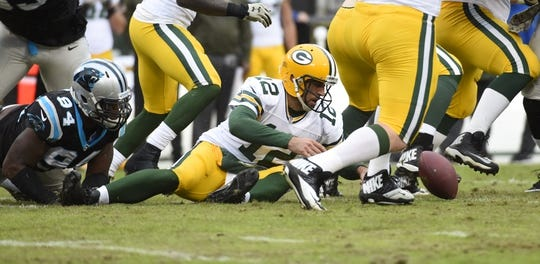 Nov 8, 2015; Charlotte, NC, USA; Green Bay Packers quarterback Aaron Rodgers (12) recaches for the ball as Carolina Panthers defensive end Kony Ealy (94) defends in the fourth quarter. The Panthers defeated the Packers 37-29 at Bank of America Stadium. Mandatory Credit: Bob Donnan-USA TODAY Sports