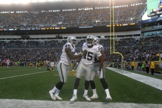 Nov 8, 2015; Pittsburgh, PA, USA; Oakland Raiders wide receiver Michael Crabtree (15) is congratulated by fullback Marcel Reece (45) and wide receiver Rod Streater (80) after scoring a touchdown against the Pittsburgh Steelers during the second half at Heinz Field. The Steelers won the game, 38-35. Mandatory Credit: Jason Bridge-USA TODAY Sports