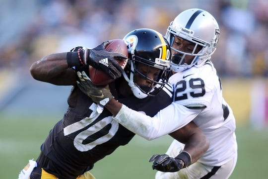 Nov 8, 2015; Pittsburgh, PA, USA; Pittsburgh Steelers wide receiver Martavis Bryant (10) secures the ball to his helmet after making a catch as Oakland Raiders cornerback David Amerson (29) defends during the third quarter at Heinz Field. The Steelers won 38-35. Mandatory Credit: Charles LeClaire-USA TODAY Sports