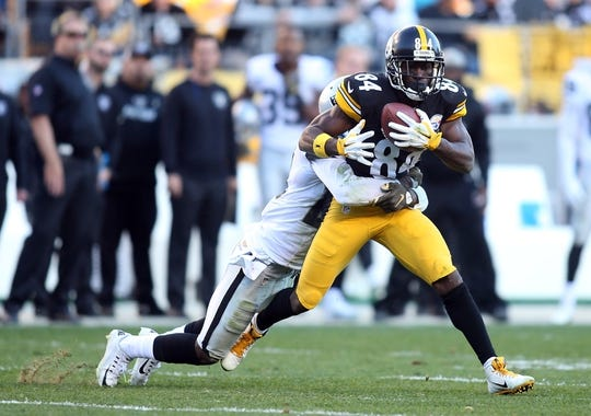 Nov 8, 2015; Pittsburgh, PA, USA; Pittsburgh Steelers wide receiver Antonio Brown (84) runs after a catch against Oakland Raiders cornerback David Amerson (29) during the third quarter at Heinz Field. The Steelers won 38-35. Mandatory Credit: Charles LeClaire-USA TODAY Sports