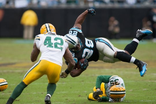 Nov 8, 2015; Charlotte, NC, USA; Carolina Panthers running back Jonathan Stewart (28) gets knocked in the air by Green Bay Packers cornerback Demetri Goodson (39) during the third quarter at Bank of America Stadium. The Panthers defeated the Packers 37-29. Mandatory Credit: Jeremy Brevard-USA TODAY Sports
