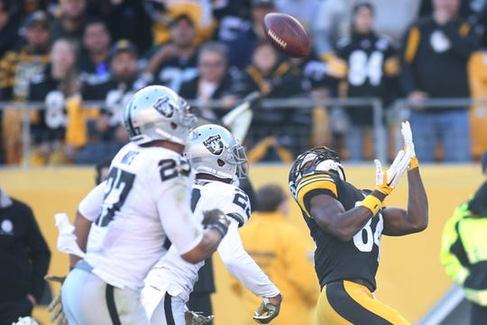 Nov 8, 2015; Pittsburgh, PA, USA; Pittsburgh Steelers wide receiver Antonio Brown (84) catches a pass behind Oakland Raiders strong safety Taylor Mays (27) and cornerback David Amerson (29) during the second quarter at Heinz Field. The Steelers won 38-35. Mandatory Credit: Charles LeClaire-USA TODAY Sports