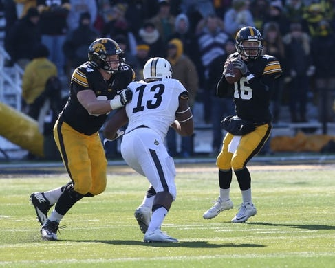 Nov 21, 2015; Iowa City, IA, USA; Iowa Hawkeyes offensive lineman Cole Croston (64) blocks Purdue Boilermakers defensive end Gelen Robinson (13) to protect  Hawkeyes quarterback C.J. Beathard (16) during the second quarter at Kinnick Stadium. Mandatory Credit: Reese Strickland-USA TODAY Sports