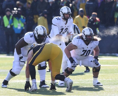 Nov 21, 2015; Iowa City, IA, USA; Purdue Boilermakers offensive lineman Martesse Patterson (74) and guard Jordan Roos (70) block for quarterback Austin Appleby (12) against the Iowa Hawkeyes during the fourth quarter at Kinnick Stadium. Iowa beat Purdue 40-20. Mandatory Credit: Reese Strickland-USA TODAY Sports