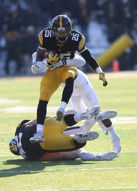 Nov 21, 2015; Iowa City, IA, USA; Iowa Hawkeyes running back Akrum Wadley (25) hurdles his own player against the Purdue Boilermakers in the third quarter at Kinnick Stadium. Iowa beat Purdue 40-20. Mandatory Credit: Reese Strickland-USA TODAY Sports
