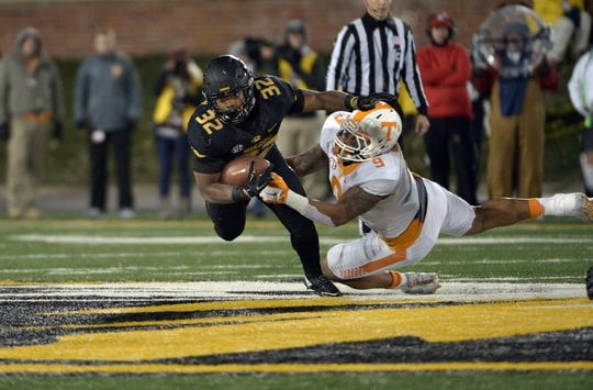 Nov 21, 2015; Columbia, MO, USA; Missouri Tigers running back Russell Hansbrough (32) is tackled by Tennessee Volunteers defensive end Derek Barnett (9) during the second half at Faurot Field. Tennessee won the game 19-8. Mandatory Credit: Denny Medley-USA TODAY Sports