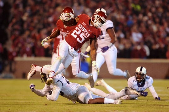 Nov 21, 2015; Norman, OK, USA; Oklahoma Sooners running back Joe Mixon (25) eludes a tackle attempt by TCU Horned Frogs linebacker Montrel Wilson (20) during the third quarter at Gaylord Family - Oklahoma Memorial Stadium. Mandatory Credit: Mark D. Smith-USA TODAY Sports