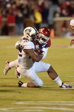 Nov 21, 2015; Norman, OK, USA; TCU Horned Frogs running back Aaron Green (22) is tackled by Oklahoma Sooners linebacker Dominique Alexander (1) during the fourth quarter at Gaylord Family - Oklahoma Memorial Stadium. Mandatory Credit: Mark D. Smith-USA TODAY Sports