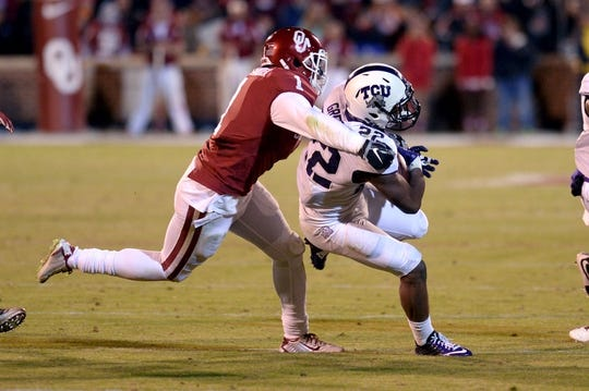 Nov 21, 2015; Norman, OK, USA; TCU Horned Frogs running back Aaron Green (22) runs the ball while being pursued by Oklahoma Sooners linebacker Dominique Alexander (1) during the fourth quarter at Gaylord Family - Oklahoma Memorial Stadium. Mandatory Credit: Mark D. Smith-USA TODAY Sports