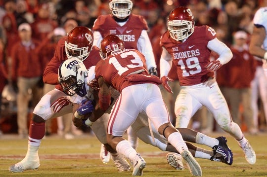 Nov 21, 2015; Norman, OK, USA; TCU Horned Frogs running back Aaron Green (22) is tackled by Oklahoma Sooners safety Ahmad Thomas (13) during the fourth quarter at Gaylord Family - Oklahoma Memorial Stadium. Mandatory Credit: Mark D. Smith-USA TODAY Sports