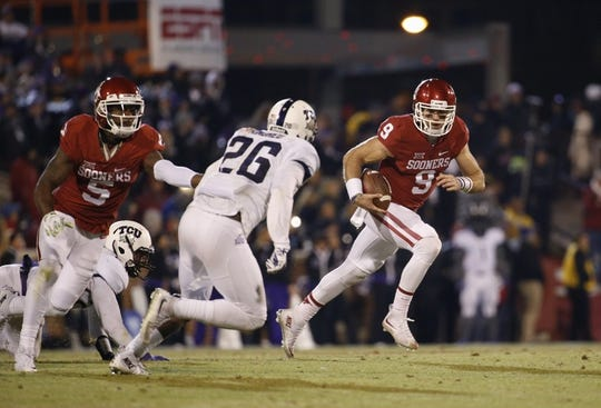 Nov 21, 2015; Norman, OK, USA; Oklahoma Sooners quarterback Trevor Knight (9) runs as TCU Horned Frogs safety Derrick Kindred (26) defends during the game at Gaylord Family - Oklahoma Memorial Stadium. Mandatory Credit: Kevin Jairaj-USA TODAY Sports