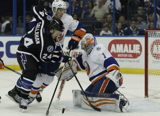 Nov 28, 2015; Tampa, FL, USA; New York Islanders defenseman Travis Hamonic (3) and Tampa Bay Lightning right wing Ryan Callahan (24) compete for the puck in front of New York Islanders goalie Thomas Greiss (1) during the second period at Amalie Arena. Mandatory Credit: Reinhold Matay-USA TODAY Sports