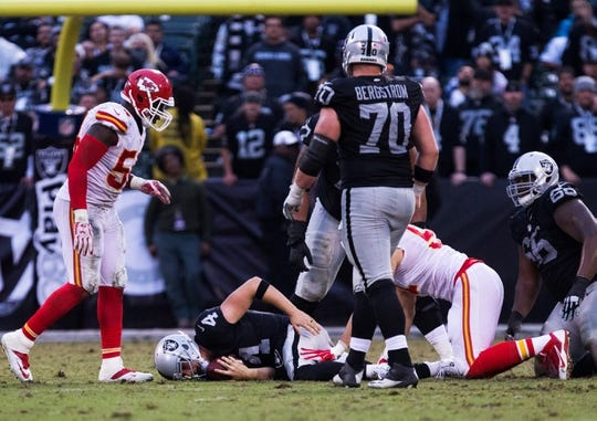 Dec 6, 2015; Oakland, CA, USA; Oakland Raiders quarterback Derek Carr (4) after being sacked by the Kansas City Chiefs during the fourth quarter at O.co Coliseum. The Kansas City Chiefs defeated the Oakland Raiders 34-20. Mandatory Credit: Kelley L Cox-USA TODAY Sports