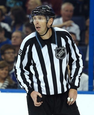 Nov 28, 2015; Tampa, FL, USA; NHL linesman Pierre Racicot (65) skates during the third period of a hockey game between the Tampa Bay Lightning and the New York Islanders at Amalie Arena.The Islanders won 3-2. Mandatory Credit: Reinhold Matay-USA TODAY Sports