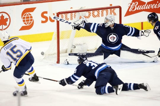 Dec 15, 2015; Winnipeg, Manitoba, CAN; Winnipeg Jets goalie Connor Hellebuyck (30) makes a stick save on St. Louis Blues center Robby Fabbri (15) during the second period at MTS Centre. Mandatory Credit: Bruce Fedyck-USA TODAY Sports