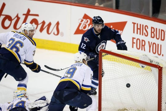 Dec 15, 2015; Winnipeg, Manitoba, CAN;  Winnipeg Jets right wing Drew Stafford (12) puts the puck past St. Louis Blues goalie Jake Allen (34) during the second period at MTS Centre. Mandatory Credit: Bruce Fedyck-USA TODAY Sports