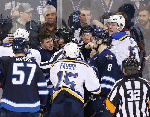 Dec 15, 2015; Winnipeg, Manitoba, CAN;  Winnipeg Jets center Mark Scheifele (55) is separated by referees after he fights with St. Louis Blues defenseman Colton Parayko (55) during the second period at MTS Centre. Mandatory Credit: Bruce Fedyck-USA TODAY Sports