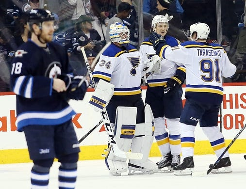 Dec 15, 2015; Winnipeg, Manitoba, CAN; St. Louis Blues goalie Jake Allen (34) celebrates with teammates after the third period against the Winnipeg Jets at MTS Centre. St. Louis Blues wins 4-3. Mandatory Credit: Bruce Fedyck-USA TODAY Sports