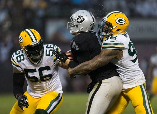 Dec 20, 2015; Oakland, CA, USA; Green Bay Packers outside linebacker Mike Neal (96) sacks Oakland Raiders quarterback Derek Carr (4) with Packers outside linebacker Julius Peppers (56) during the fourth quarter at O.co Coliseum. The Green Bay Packers defeated the Oakland Raiders 30-20. Mandatory Credit: Kelley L Cox-USA TODAY Sports