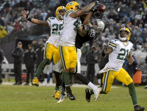 Dec 20, 2015; Oakland, CA, USA; Oakland Raiders wide receiver Amari Cooper (89) is defended by Green Bay Packers cornerback Casey Hayward (29) and strong safety Morgan Burnett (42) and free safety Ha Ha Clinton-Dix (21) during an NFL football game at O.co Coliseum. The Packers defeated the Raiders 30-20. Mandatory Credit: Kirby Lee-USA TODAY Sports