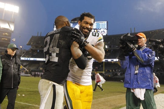 Dec 20, 2015; Oakland, CA, USA; Green Bay Packers outside linebacker Julius Peppers (56) meets with Oakland Raiders safety Charles Woodson (24) after the game at O.co Coliseum. The Packers defeated the Raiders 30-20. Mandatory Credit: Cary Edmondson-USA TODAY Sports