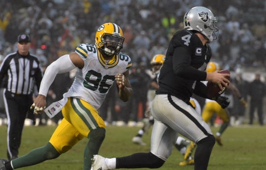 Dec 20, 2015; Oakland, CA, USA; Green Bay Packers outside linebacker Mike Neal (96) pressures Oakland Raiders quarterback Derek Carr (4) during an NFL football game at O.co Coliseum. The Packers defeated the Raiders 30-20. Mandatory Credit: Kirby Lee-USA TODAY Sports