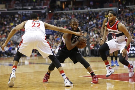 Dec 28, 2015; Washington, DC, USA; Los Angeles Clippers guard Chris Paul (3) holds the ball as Washington Wizards forward Otto Porter Jr. (22) and Wizards guard Garrett Temple (17) defend in the second quarter at Verizon Center. The Clippers won 108-91. Mandatory Credit: Geoff Burke-USA TODAY Sports