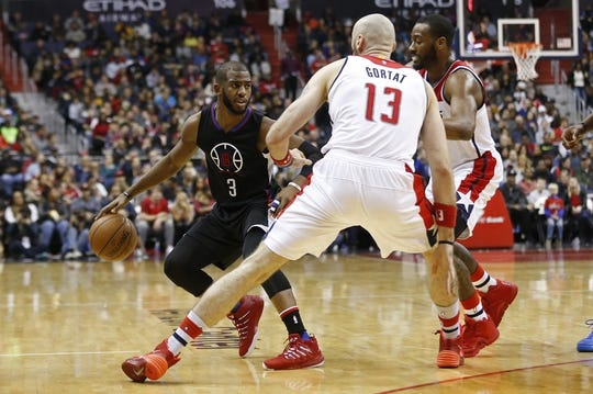 Dec 28, 2015; Washington, DC, USA; Los Angeles Clippers guard Chris Paul (3) dribbles the ball as Washington Wizards center Marcin Gortat (13) and Wizards guard John Wall (2) defend in the second quarter at Verizon Center. The Clippers won 108-91. Mandatory Credit: Geoff Burke-USA TODAY Sports