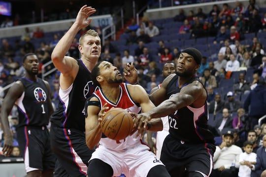 Dec 28, 2015; Washington, DC, USA; Washington Wizards guard Garrett Temple (17) shoots as Los Angeles Clippers forward Branden Dawson (22) and Clippers center Cole Aldrich (45) defend in the fourth quarter at Verizon Center. The Clippers won 108-91. Mandatory Credit: Geoff Burke-USA TODAY Sports