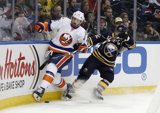 Dec 31, 2015; Buffalo, NY, USA; New York Islanders right wing Cal Clutterbuck (15) and Buffalo Sabres right wing Brian Gionta (12) battle for the puck during the first period at First Niagara Center. Mandatory Credit: Timothy T. Ludwig-USA TODAY Sports