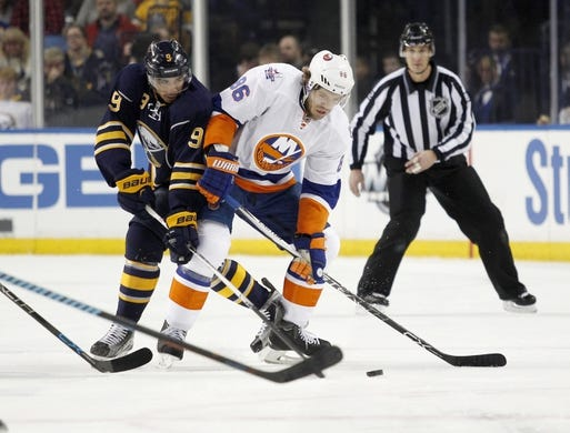 Dec 31, 2015; Buffalo, NY, USA; Buffalo Sabres left wing Evander Kane (9) and New York Islanders left wing Nikolay Kulemin (86) battle for the puck during the first period at First Niagara Center. Mandatory Credit: Timothy T. Ludwig-USA TODAY Sports