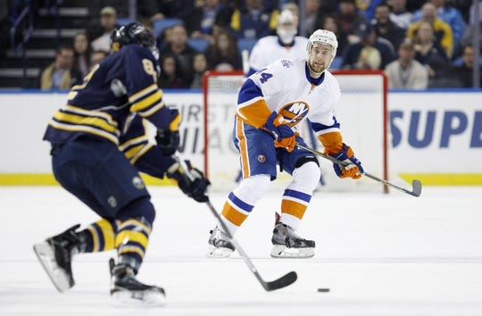 Dec 31, 2015; Buffalo, NY, USA; Buffalo Sabres left wing Marcus Foligno (82) skates with the puck in front of New York Islanders defenseman Calvin de Haan (44) during the first period at First Niagara Center. Mandatory Credit: Timothy T. Ludwig-USA TODAY Sports