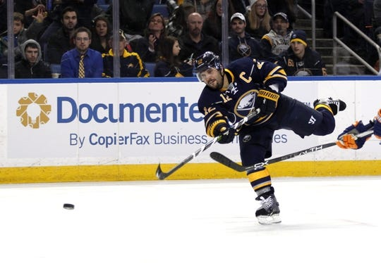 Dec 31, 2015; Buffalo, NY, USA; Buffalo Sabres right wing Brian Gionta (12) takes a shot on goal during the second period against the New York Islanders at First Niagara Center. Mandatory Credit: Timothy T. Ludwig-USA TODAY Sports
