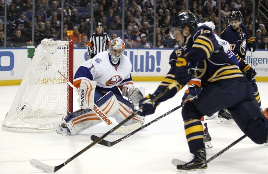 Dec 31, 2015; Buffalo, NY, USA; New York Islanders goalie Thomas Greiss (1) watches as Buffalo Sabres center Jack Eichel (15) carries the puck during the second period at First Niagara Center. Mandatory Credit: Timothy T. Ludwig-USA TODAY Sports