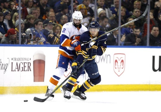 Dec 31, 2015; Buffalo, NY, USA; New York Islanders defenseman Nick Leddy (2) and Buffalo Sabres center Sam Reinhart (23) go after a loose puck during the second period at First Niagara Center. Mandatory Credit: Timothy T. Ludwig-USA TODAY Sports