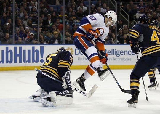 Dec 31, 2015; Buffalo, NY, USA; New York Islanders center Anders Lee (27) jumps in front of Buffalo Sabres goalie Linus Ullmark (35) to avoid a shot during the third period at First Niagara Center. Islanders beat the Sabres 2-1. Mandatory Credit: Timothy T. Ludwig-USA TODAY Sports