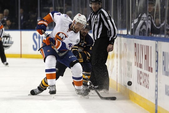 Dec 31, 2015; Buffalo, NY, USA; Buffalo Sabres right wing Brian Gionta (12) watches as New York Islanders defenseman Calvin de Haan (44) shoots the puck up ice during the third period at First Niagara Center. Islanders beat the Sabres 2-1. Mandatory Credit: Timothy T. Ludwig-USA TODAY Sports