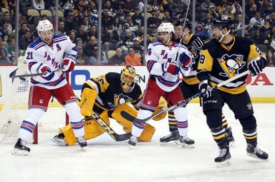 Feb 10, 2016; Pittsburgh, PA, USA; New York Rangers center Derek Stepan (21) attempts a tip as Pittsburgh Penguins goalie Marc-Andre Fleury (29) and defenseman Kris Letang (58) defend during the first period at the CONSOL Energy Center. Mandatory Credit: Charles LeClaire-USA TODAY Sports