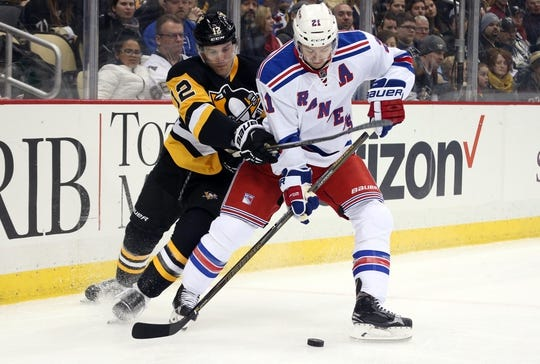 Feb 10, 2016; Pittsburgh, PA, USA; New York Rangers center Derek Stepan (21) handles the puck against pressure from Pittsburgh Penguins defenseman Ben Lovejoy (12) during the first period at the CONSOL Energy Center. Mandatory Credit: Charles LeClaire-USA TODAY Sports