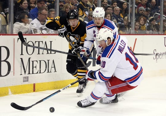 Feb 10, 2016; Pittsburgh, PA, USA; New York Rangers center J.T. Miller (10) controls the puck ahead of right wing Jesper Fast (19) and Pittsburgh Penguins defenseman Olli Maatta (3) during the first period at the CONSOL Energy Center. Mandatory Credit: Charles LeClaire-USA TODAY Sports